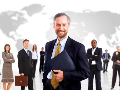 Imagem mostra homem de terno segurando uma pasta e atrás outras pessoas trabalhando